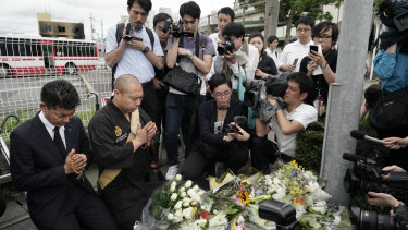 Japanese Diet member, Kenta Izumi, left, and Buddhist monk, Matsumoto Genkun, pay respects at a makeshift memorial outside the Kyoto Animation studio.