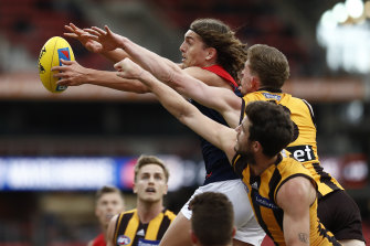 Pole position: Melbourne's Luke Jackson fends off a pair of Hawks.