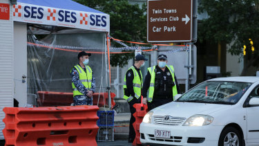 Police and defence personnel check on cars crossing the Qld-NSW border at Coolangatta.