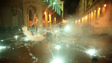 Anti-government protesters throw firecrackers against the riot police, background, in downtown Beirut, Lebanon, on Sunday.