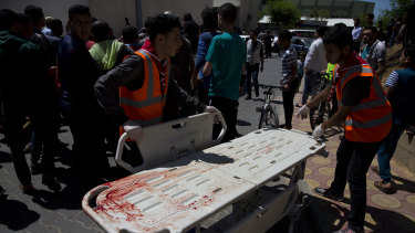 Palestinian medics stand by a bloodied stretcher outside a morgue in Beit Lahiya, Gaza Strip on Monday.