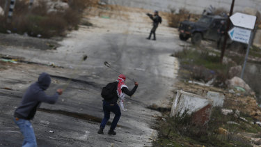 Palestinian demonstrators throw stones during clashes with Israeli security forces as they protest the Trump Middle East peace plan at Beit El checkpoint, near the West Bank city of Ramallah.