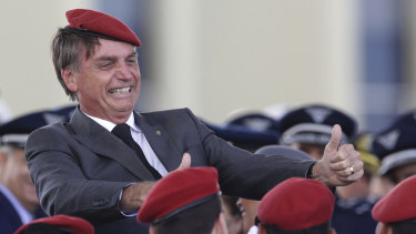 Jair Bolsonaro flashes two thumbs up as he poses for a photo with cadets during a ceremony marking Army Day, in Brasilia, Brazil.