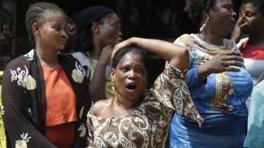 A woman cries as the body of a child is recovered from the rubble of a collapsed building in Lagos, Nigeria.