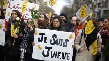 """A woman carries a poster reading """"I am a jew"""" as she attends a silent march to honour an 85-year-old woman who escaped the Nazis 76 years ago but was stabbed to death last week in her Paris apartment, apparently because she was Jewish."""