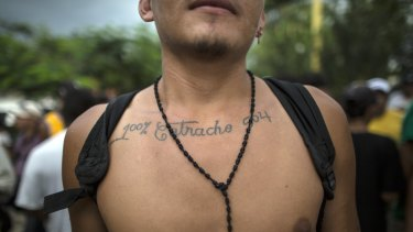 """Honduran migrant Jose Santos Izaguirre shows his tattoo that reads in Spanish: """"Hundred percent Catracho 504,"""" with Catracho referring to his nationality and the number 504 is Honduras' country code."""