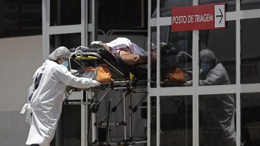 Health workers push a patient suspected of having COVID-19 into the HRAN Hospital in Brasilia, Brazil, on Thursday.
