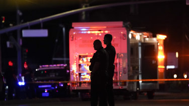 Two police officers stand outside the office building where a shooting occurred in Orange, California,