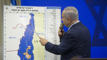 Benjamin Netanyahu points to a redrawn map in September as he pledged to annex the Jordan Valley in occupied West Bank if re-elected. The move would leave West Bank Palestinians with only a landlocked island, in orange, within Israel.