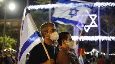 A couple wearing masks for protection against the spread of the coronavirus hold Israeli flags during a protest against the government and the corruption, at Rabin square in Tel Aviv, Israel.