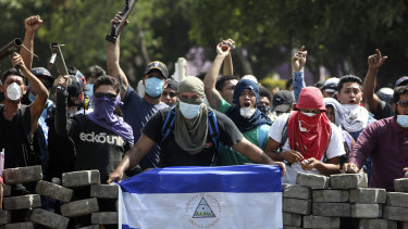 Masked protesters, one with a Nicaraguan flag, yell from the road block they erected as they face off with security forces near the University Politecnica de Nicaragua in Managua on Saturday.