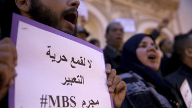 """An activist holds up a placard that reads """"No to repression of freedom of expression #MBS criminal"""" on the eve of Saudi Crown Prince Mohammed bin Salman's official visit to Tunisia."""