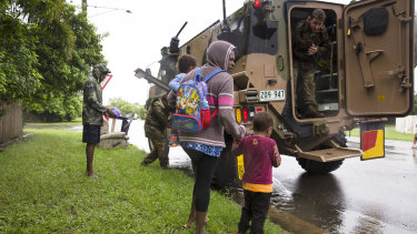 Army personal assist a family evacuating rising flood waters in Rosslea, Townsville.