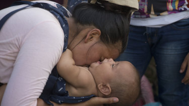 Daisy Zuniga, a migrant from Honduras, plays with her baby Glinder in a shelter in Chiquimula, Guatemala. They are part of a group walking toward the US.