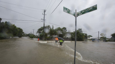 Residents walking through flooded waters in Hermit Park Townsville on Sunday.