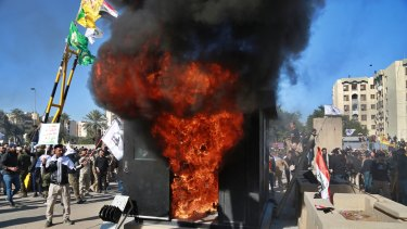 Protesters burn property in front of the US embassy compound, in Baghdad.