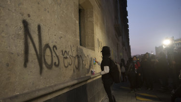 "A protester sprays the ""They're killing us"" on the exterior of the National Palace in Mexico City."