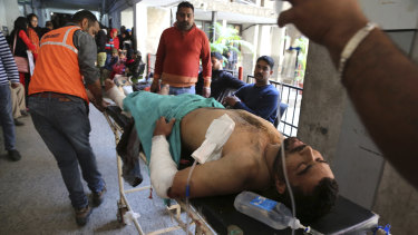 A person injured in a grenade attack is carried for treatment to a government medical hospital in Jammu on Thursday.
