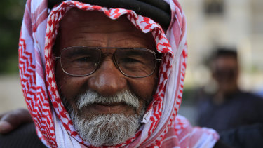 A Syrian man poses for a picture as he gathers with his family in the Marjeh Square, in Damascus, Syria, on Sunday.