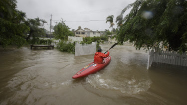 A local resident is seen kayaking in flood waters at her home in Hermit Park Townsville on Sunday.