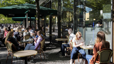 People sit at tables outside a cafe at Kungstrdgrden in Stockholm, Sweden.