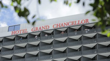 Guests at the Hotel Grand Chancellor stand on their balconies ahead of an extended stay in hotel quarantine.