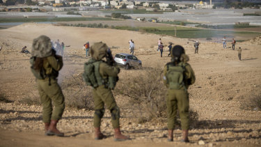 Palestinians and Israeli activists run away from tear gas fired by Israeli soldiers during a demonstration against the construction of Jewish settlements in the Jordan Valley.