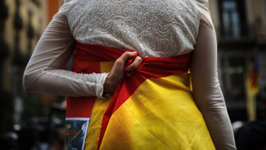 A woman holds a Spanish flag around her body during a ceremony marking the first anniversary of a terror attack in Las Ramblas promenade in Barcelona, Spain.