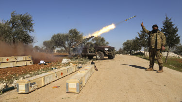 Rebel fighters fire a missile towards Syrian government positions in the province of Idlib.