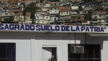 """The Spanish phrase """"Sacred soil of the fatherland"""" covers an administrative office at a wholesale food market, near a shantytown in Caracas, Venezuela."""