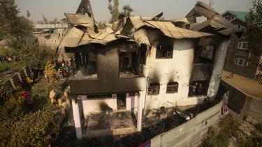 Kashmiris assemble near a damaged house after a gun battle in Srinagar on Wednesday.