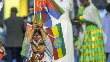 A child holds Ethiopian and Eritrean flags in Addis Ababa, Ethiopia. Official rivals just weeks ago, the leaders of Ethiopia and Eritrea embraced warmly to the roar of a crowd of thousands at a concert celebrating the end of a long state of war.