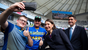 NSW Premier Gladys Berejiklian and Skills Minister and member for Parramatta Geoff Lee pose for a selfie with supporters at the Bankwest Stadium Open Day on Sunday.