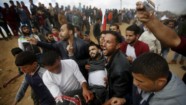 Palestinian protesters evacuate a wounded youth during clashes with Israeli troops along the Gaza Strip border with Israel, on Friday.