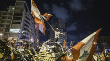 An anti-government protester waves a Lebanese flag as he stands on top of a pile of broken tents in Martyrs' Square, Beirut, on October 29.
