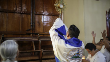 Father Harvey Padilla exposes the consecrated host to one of the barricaded doors of the San Juan Bautista Church after supporters of President Daniel Ortega attempted to enter the church by force.