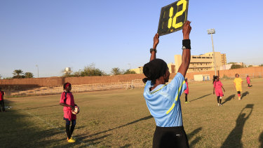A referee holds a board as Sudanese al-Difaa, in pink, and al-Sumood women's teams play in Omdurman.
