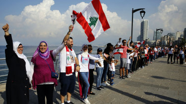 Anti-government protesters form a human chain as a symbol of unity, during ongoing protests against the Lebanese government, on the Mediterranean waterfront promenade, in Beirut, Lebanon.
