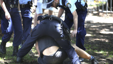 Police outside Field Day attempt to make a man open his mouth.