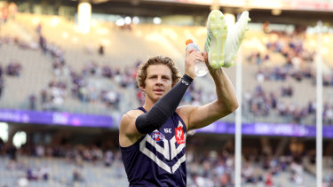 Fill your boots: Nat Fyfe salutes the crowd at Optus Stadium after the Dockers' round 1 thrashing of the Roos.