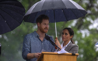 Under cover: Harry and Meghan take shelter at a community picnic at Dubbo in 2018.