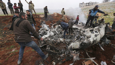 Syrians gather around a wreckage of a government military helicopter that was shot down in the countryside west of the city of Aleppo.
