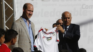 Head of the Palestinian Football Federation, Jibril Rajoub, presents a national team's football jersey to Prince William in Ramallah.