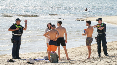 Police officers inform beachgoers at Brighton of closures on Saturday.