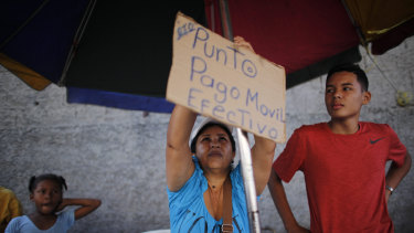 "Daixy Aguero puts up a sign that reads in Spanish ""Point of sale, mobile payment and cash,"" at her stand where she sells beauty products, at a market in Caracas, Venezuela."