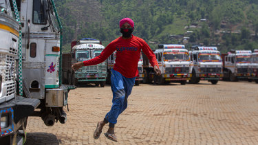 A stranded truck operator playfully jumps near parked trucks during the nationwide lockdown in Gauhati, India.