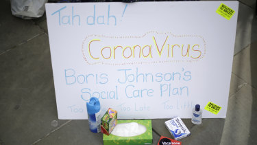 Anti-Brexit campaigners hold placards including references to the outbreak of coronavirus as they protest outside Parliament in London on Wednesday.