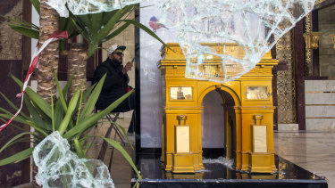 A replica of the Arc de Triomphe is pictured through the smashed window of a perfumery the day after riots erupted on the Champs Elysee.