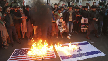 Shiite Muslims burn representations of US and Israeli flags near the US consulate in Lahore, Pakistan in protest over the air strike that killed the Iranian general.