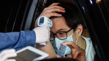 A man has his temperature taken at a drive through COVID-19 testing centre at Vibhavadi Hospital in Bangkok, Thailand.